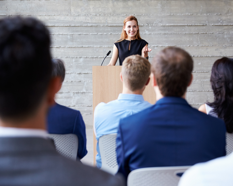 Business woman speaking in front of a group of people
