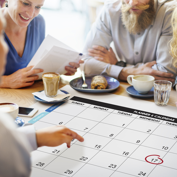 Group of people sitting at a table looking at a calendar